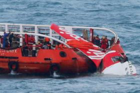 In this file photograph taken on January 10, 2015, Indonesian search and rescue personnel pull wreckage of AirAsia flight QZ8501 onto the Crest Onyx ship at sea.