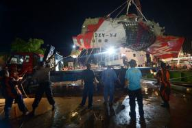 Workers prepare to load the tail section of Air Asia Airbus A320 flight QZ8501 onto a truck at port in Kumai on Jan 11. Indonesian divers found the crucial black box flight recorders of the AirAsia plane that crashed in the Java Sea.