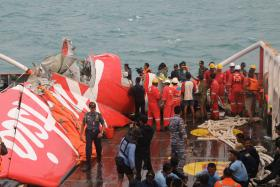 File photo of the plane's wreckage being lifted into a ship at sea south of Borneo island.