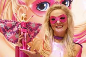 A young woman, dressed as a 'Barbie' doll, poses with a new 'Barbie' doll during the press preview of the 66th International Toy Fair in Nuremberg .  Can it revive Mattel's fortune though?