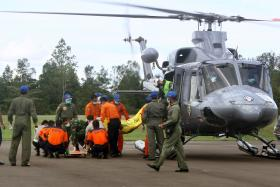 Indonesian rescue personnel unload body bags from a military helicopter in Pangkalan Bun on January 22, 2015 containing bodies recovered from the underwater wreckage of ill-fated AirAsia flight QZ8501.