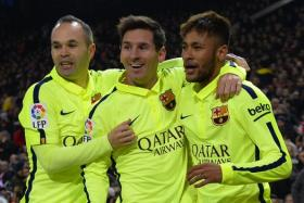 Barcelona's Brazilian forward Neymar da Silva Santos Junior (R) celebrates with Barcelona's midfielder Andres Iniesta (L) and Barcelona's Argentinian forward Lionel Messi after scoring.