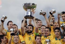 Australia captain Mile Jedinak (C) holds up the Asian Cup trophy as the team celebrates after winning their Asian Cup final soccer match against South Korea at the Stadium Australia in Sydney on Jan 31.