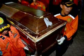 Members of an Indonesian rescue team carry a coffin with the remains of a victim of the AirAsia flight QZ8501 accident, in Makassar, South Sulawesi, on Jan 30.