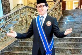 Not a stunt:  Chan posing for cameras after receiving his Datukship.