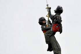 MISSION: (Above) Sgt Goh Zhe-Wen being winched up to a Super Puma helicopter, along with a crew member pretending to be injured and with a mock casualty.