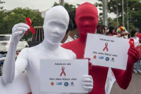 Two activists showing red ribbons, the symbol of HIV/Aids awareness, during a campaign in Surabaya, Indonesia, in December last year