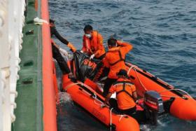 In this photograph taken on Feb 2, Indonesian rescue personnel from the National Search and Rescue Agency recover a body from the underwater wreckage of the ill-fated Air Asia flight QZ8501.