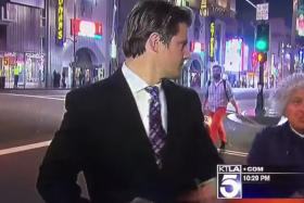 American reporter Steve Kuzj deals with a man who tried to interfere with his live news report.