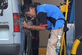 SCAMMED: Mr Tan Soy Kiang, who cannot stand up straight due to a spinal injury, works as both a cleaner and pump attendant to repay his 'debt'.