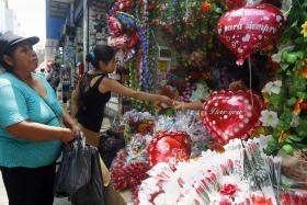 People buy heart-shaped balloons and artificial flowers from a stand ahead of Valentine's Day outside the Central Market in downtown Lima.