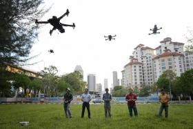 FLY AWAY: (From left) PhD researcher Ervine Lin, lawyer Roe Yun Song, tutor Gan Weili, medical technologist Alvin Wong and IT engineer Aramid Lee flying their drones at Tanjong Rhu.