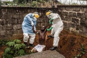 COMPELLING: US photographer Pete Muller, on assignment for National Geographic/The Washington Post, won the first prize in the general news category (stories). His series of pictures includes this one of medical staff at the Hastings Ebola Treatment Center escorting a man in the throes of ebola-induced delirium back into the isolation ward from which he escaped, in Freetown, Sierra Leone.