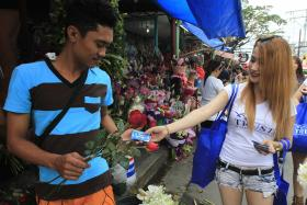 A man receives a pack of condoms from a model, as part of a promotional gimmick, on the eve of Valentine's Day in Manila