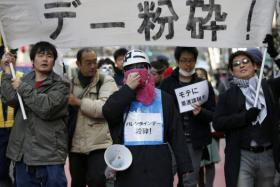 """Protesters from the Revolutionary Alliance of Men that Women find Unattractive hold a banner reading """"Smash Valentine's Day"""" as they shout slogans during a march in Tokyo."""