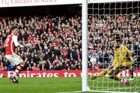 Arsenal's Olivier Giroud (left) shoots to score his first goal past Middlesbrough goalkeeper Tomas Mejias during their FA Cup fifth round soccer match at the Emirates Stadium in London February 15, 2015.