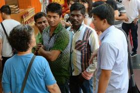 WAIT: Three foreign workers were spotted in the queue at New Bridge Road yesterday.
