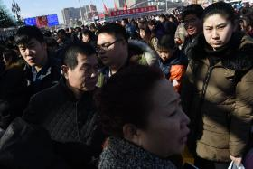 Passengers wait to enter Beijing railway station on Tuesday. Hundreds of millions of Chinese are returning to their hometowns to celebrate the New Year with families.