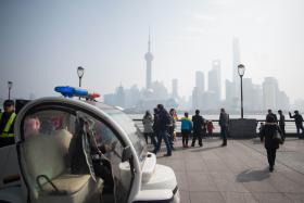 A police officer drives a golf cart as he patrols  the promenade on the Bund  in Shanghai on Wednesday