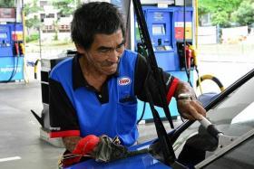 BUSY: Mr Tan Soy Kiang hard at work at the Esso petrol station at Toa Payoh Lorong 2 yesterday.