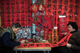 A man writing Chinese calligraphy in preparation for the Chinese New Year celebrations in Hong Kong.