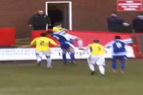 Worcester City player Shab Khan (No. 3) reacts to a challenge by Stockport County's Charlie Russell - by body slamming him.