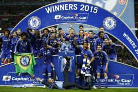 SHOW STEALER: Jose Mourinho (bottom) can't hide his joy at winning the League Cup as his Chelsea players celebrate with the trophy.