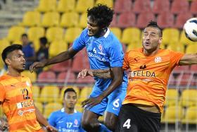 MAGNIFICENT MADHU: LionsXII defender Madhu Mohana (No. 6) challenging for a header with Felda's Bojan Miladinovic as Shukor Adan (No. 12) looks on.