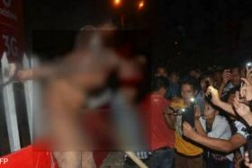 A crowd surrounds an alleged rapist after he was dragged out of prison and beaten to death in Dimapur in the northeastern Indian state of Nagaland on March 5.