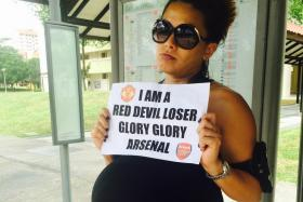 ONE FM 91.3 deejay Cheryl Miles at a bus stop in Bishan while fulfilling her end of a dare after Manchester United lost to Arsenal.