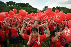 Toddler getting a lift from her father as they help form the SG Heart Map at Bishan-Ang Mo Kio Park on March 14 before the first concert in the park, in the National Parks Board's SG50 series.