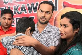 Jellinah Swari and her husband Dinesh Raja (second right) holding their son after the press conference at the Perai DAP service centre.