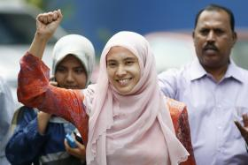 Nurul Izzah raises her fist as she is released on bail from a police station in Kuala Lumpur on Tuesday
