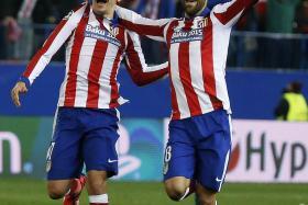 Atletico Madrid's Antoine Griezmann and Jesus Gamez celebrate winning in penalty shootout against Bayer Leverkusen.