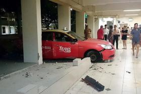 ACCIDENT: (Above) Residents examine the scene at a Yishun HDB block after a taxi reversed into the void deck.