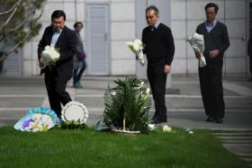 People arriving with flowers to pay their respects to Mr Lee Kuan Yew, in the gardens of the Singapore Consulate in Shanghai on Monday