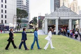 IN STRIDE: Wax figures of The Beatles in Raffles Place yesterday, in poses reminiscent of the English rock band's famous Abbey Road album cover.