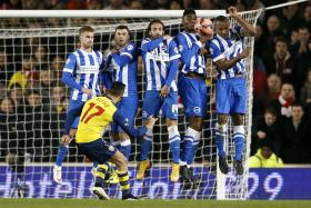 Arsenal's Alexis Sanchez (left) takes a free kick during their FA Cup fourth round soccer match against Brighton and Hove Albion early this year
