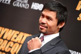 Boxer Manny Pacquiao poses on the red carpet before a joint press conference with Floyd Mayweather Jr on March 11, 2015 at the Nokia Theatre at LA Live in Los Angeles, California. Mayweather and Pacquiao are scheduled to fight May 2, 2015 in Las Vegas.