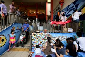 306 students from 18 classes of Diploma Level 1 Foundation Certificate in Visual Arts of LASALLE College of the Arts painting wall murals at 3 hawker centres nearby the Campus