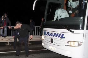 The injured driver of Fenerbahce's football team bus holds his head after the attack on Saturday