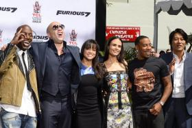 Vin Diesel (second from left) and the cast of Fast & Furious 7 have every reason to smile after the film broke records at the US box office on its opening weekend.