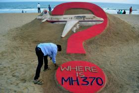 Indian sand artist Sudarsan Pattnaik creating a sand sculpture of the missing Malaysian airliner MH370 on Puri beach in eastern Odisha state on March 7