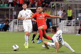 GOOD AND BAD: Sahil Suhaimi dribbling past former LionsXII defender Baihakki Khaizan (on ground), who was later sent off for a second yellow card.