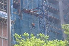 SCDF officers retrieving a body on Friday morning (April 17) from a crane at a construction site at Queen Street.
