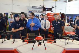 Singapore Civil Defence Force's Captain Jennyline Fan and Commissioner Eric Yap introduce the drones to Second Minister for Home Affairs S Iswaran at the SCDF workplan seminar.