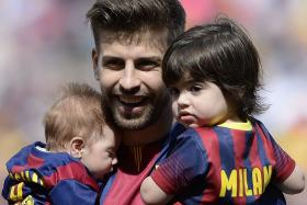 Barcelona's defender Gerard Pique holds his sons Milan and Sasha during the Spanish league football match FC Barcelona v Valencia CF at the Camp Nou stadium in Barcelona on April 18, 2015.