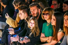 Former footballer David Beckham with his daughter, Harper, on his lap during a presentation of the Victoria Beckham Fall/Winter 2015 collection during New York Fashion Week on Feb 15.