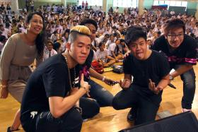 INSPIRING: Shigga Shay and Gentle Bones pose for a picture with the event's emcees and students at Bishan Park Secondary School (above) yesterday.