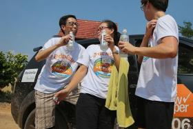 BE COOL: Participant Alvin Yeong and his family quenched their thirst with isotonic drinks when they took part in the 2014 The New Paper SUVival Challenge.